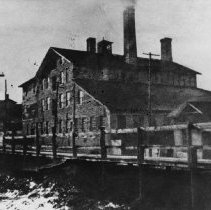 Image of John Doty's Foundry, circa 1851 - The foundry was located on Lakeshore Road, on the west side of Sixteen Mile Creek, immediately north of the Lakeshore Road bridge and east of Forsyth Street.  Shows the actual building as erected in 1851.  In 1877 it was bought by William Robertson.  Office on the right was moved and remodelled into No. 9 Second Street.  The Carriage Works was demolished 1903.