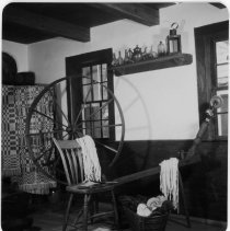 Image of Interior of Thomas House - The interior of the Thomas House after it was moved to Front Street in 1955. Picture of the spinning wheel. See also 1950.3.202.