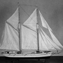 Image of White Oak Model - This is a model of the White Oak schooner. It was built by R. W. Davis for the Centennial Project in 1967. The actual boat was built by Duncan Chisholm for his brother, Captain George. It was launched from Oakville in 1867 on the first Canada Day. It carried many cargos under many masters throughout the years and when it was no longer useful it was allowed to fall apart at Collins Inlet on the north shore of Georgian Bay. This photo was used on postcards.