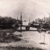 Image of Oakville Harbour - Oakville Harbour at high water in 1906. Shows the Aberdeen Bridge and multiple sailing vessels as well as various sheds. The Lighthouse and Marlatt and Armstrong's Tannery can be seen in the background.