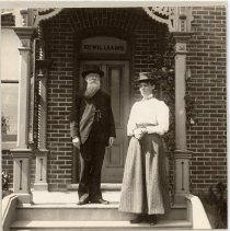 Image of Dr. and Mrs. Justus Samuel Wright Williams - Dr. and Mrs. J. S. W. Williams in front of their office/house shortly after their marriage. Mrs Jennie Williams was Miss Jennie McGill. Dr. J. S. W. Williams was the son of Justus Wright Williams. He studied at the Oakville Common and Grammar Schools as a child and went on to graduate from the Victoria Medical School in 1867, after which he returned to Oakville to practice his profession. In 1885 he was appointed the Medical Health Officer and Coroner of Oakville, positions that he held until his death. He lived in a house that he built on the south-west corner of Dundas Street and Colborne Street, until his death.