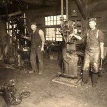 Image of Whitaker's Blacksmith Shop - Interior of Whitaker's Blacksmith Shop, now Whitaker's Garage, in the early 1900's. Shown in the picture are Jack (Kitty) Whitaker and Albert (Ab) Hughes.