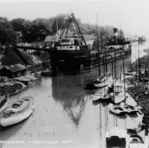 Image of Oakville Harbour - A ship, the Coal Haven, docked and unloading coal. The ship is part of Canada Steamship Lines. Used as a postcard.