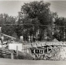 Image of Unidentified Bridge - Cement truck (far left) preparing to pour concrete onto a bridge during construction. Seven unidentified workers are also included in the photograph.