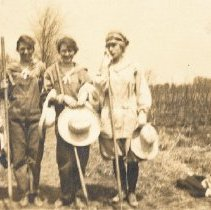 """Image of """"Farmerettes"""" - Four unidentified young women. It is likely that the farm was run by women during wartime, who stepped in to keep everything running (since most of the men were overseas). Exact date and location are both unknown."""