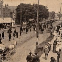 Image of Parade on Colborne - Parade on Colborne St. Oakville, Several Horse drawn buggies are on the road and lots of people are walking around.  The parade is unidentified with its banners.