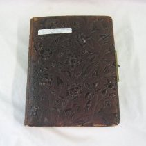 "Image of 2009.491.1 - Yearbook with brown leather cover embossed on front and back with ornate floral motif. Book contains black and white photos of members of Hudson High School's Class of 1885, which included nine women and five men. One photo depicts stage upon which the June 19, 1885 graduation ceremony was held, including the class motto: ""Aid Thyself."" Scanned image of graduation invitation, including the names of all the graduates, is attached here. 