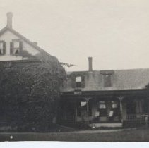 """Image of 2006.042.115 - Front view of a large house built in a """"U"""" shape - two chimneys.  A gentleman is in the foreground at the left-hand side of the photo.  The left side of the home is vine covered and three stories high and a two story ell divides the two stories side from it.  There are rocking chairs on the porch."""