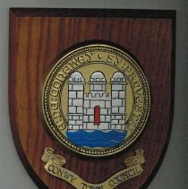 Image of Heraldic Shield - Heraldic Shield (medallion on wooden shield shaped plaque with letter explaining the context of the gift. Letter explains that item was gifted to them from Conway Wales to present to the Conway (New Hampshire) Public Library in June 12, 1992.