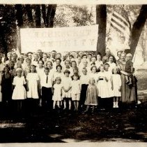 Image of LaCrescent Community, group by trees with flag and banner. - Local Church