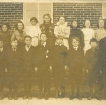 Image of East School Students 1907 - Sepia Photograph showing 16 students with teacher in front of school building.  Dated on back as 1907.  Back of photo identifies 4 boys:  Stuart Grant, Paul Barker, Murray Boess, & Morris Pitt.