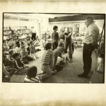 Image of Officer Ken Zandrowicz - Bicycle education class at West School with Officer Ken Zandrowicz. Sue Zandrowicz is standing in front of him with her arms extended.