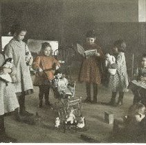 Image of Play hour at the orphanage - Colored postcard of little girls with dolls in a room.  Irene Butler, Gertrude James, Anna Ollberg, Elsie Flowers, Mary Ellen, Uno Lake.