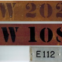 Image of Identifying room number signs from East School. E 112 denotes a room in the east wing, and 