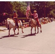 Image of Horseback riders in the 1976 parade from left - Two women on horseback with an American flag in the 1976 Bicentennial Parade