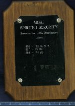 Image of Award dark wood color with balck metal plate with lettering Most spirited sorority sponsored by A. C. cheerleaders 1986-Delta Zeta, 1987 Phi Mu, 1988 Phi Mu - Award
