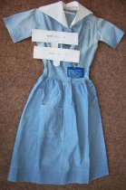 Image of Blue cotton shirt waist uniform dress, one piece.  Has short sleeves.  Has a patch on the left and right back shoulders.  Has two back pockets.  Has snap front placket.  White detachable collar and  (2) cuffs with button tab size 10 1/2.  - nurses uniform dress