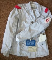 Image of Gray and white pinstripe cotton jacket. Has U. S. Cadet nurse patch on the left sleeve. Has red buttoned on shoulder bands.  With cadet nurse corp embalm pin on the left shoulder. Has 4 metal cadet nurse corp embalm down the front. Has two button patched pockets. Is long sleeved. Has one copy of white color Gideon new testament.  - nurses uniform dress