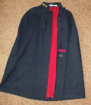 Image of Navy blue wool cape with red flannel lining has two button tabs used for fastening. Has inside pocket.  Has stand up collar with embroidered initials MGH. - nurses uniform dress