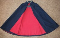 Image of Navy blue wool cape with red flannel lining has two button tabs used for fastening. Has inside pocket.  Has stand up collar with embroidered initials MGH.  Has name E. Enzor embroidered inside. - nurses uniform dress