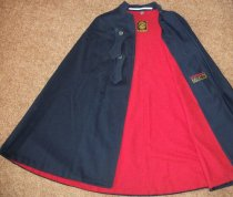 Image of Navy blue wool cape with red flannel lining has two button tabs used for fastening. Has inside pocket.  Has stand up collar with embroidered initials MGH on left side.  Has sewn on initials LLD - nurses uniform dress
