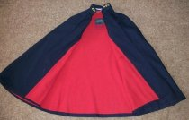 Image of Navy blue wool cape with red flannel lining has two button tabs used for fastening. Has inside pocket.  Has stand up collar with embroidered initials MGH.  Has embroidered name M. Bunn. - nurses uniform dress