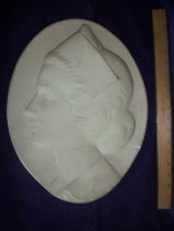 Image of Plaster relief plaque, cream color, in the shape of a nurse.  - Plaque