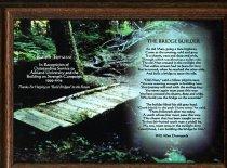 Image of Award framed has scene of forest and bridge.