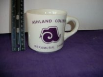 """Image of Cup white color with purple color lettering.  Has the following """"Ashland College Intramural Champ"""".  On the reverse is signed best wishes, Ralph Tomassi 7-2012. - Objects Collection"""