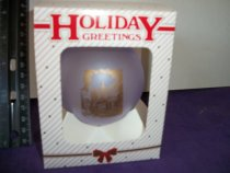 Image of Holiday ornament round glass shape purple color in a gift box.  Ornament has an image of Memorial Chapel with the library building.   - Objects Collection