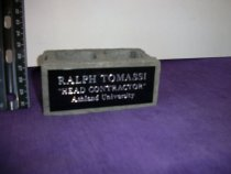 """Image of Small artifical cinder block has an attached plate engraved """"Ralph Tomassi """"Head Contractor"""" Ashland University"""". - Objects Collection"""