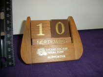 Image of Smal wooden desk calendar has the name Ashland College Annual Fund Supporter stamped in gold color. - Objects Collection