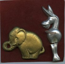 Image of Small plaster relief  gold colored elephant and silver colored donkey attached to felt card.   - Objects Collection