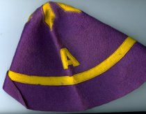 Image of Ashland College Beanie/Dink hat, purple color with gold colored accent band and letter A.  - Objects Collection