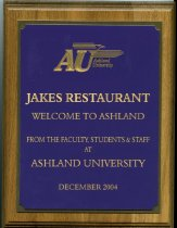 Image of Award/plaque wood with metal attached plate in purple color has gold lettering Jakes restaurant welcome to Ashland from the Faculty, Students & Staff at Ashland University December 2004. - Award