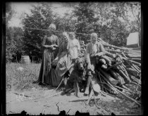 Image of [Group seated by a woodpile] - Negative, Glass-plate