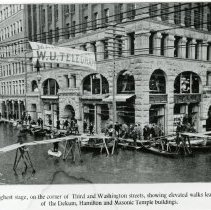 """Image of Print, Photographic - Copies: 1 ( 1 copy)   """"The water at its highest stage, on the corner of Third and Washington streets, showing elevated walks leading to the entrances  of Dekum, Hamilton, and Masonic Temple buildings.""""  (front of image)"""
