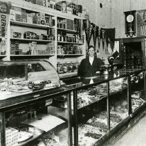 """Image of Print, Photographic - Copies:  1 (1 copy)  """"Joseph Keppinger in Confectionary Store and telephone switchboard at Gervais 1909.""""(back)"""