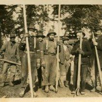 """Image of Print, Photographic - Copies: 3 (2 originals, 1 copy)  """"1 _____ 2 Louis Labonte 3 ______ 4 Fred Raymond 5 (Raymond- Augustin II ?) (the one that got ran over) 6 _____ 7 Lambert """" (back of one original)  """"Piling Camp L - R. - unknown Louis Labonte Jr. - unknown Fred Raymond Louis Labonte - father of Jr. - unknown Frank Lambert"""" (back of copy, written by H. Munnick)  * the identification of the fifth man is based off the original; this man does not resemble Louis LaBonte Sr. *"""