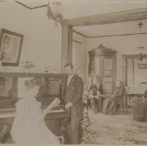 """Image of Card, Cabinet - Staged photograph of an interior house. Possibly the Moores' house. """"Mother and Father"""" is written on the back of the mount. It does not indicate who in the photo is 'mother and father'."""