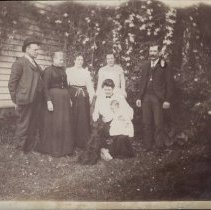 Image of Print, Photographic - Family photo of the Stinson's. Louis R. Stinson stands at the end on the left. His wife is crouched in the front with their son, Logan. Location unknown, but most likey they are in their hometown of Salem.