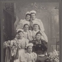 Image of Card, Cabinet - Studio photo of seven young women; all bearing a pin on the left breast of a star (possibly Order of the Eastern Star). Allie Stinson is seated in the second row next to the girl in black.