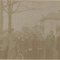Image of Card, Cabinet - Photo of Irene and another young woman with an unidentified group of men. Men to the left are posing with a skeleton wearing a hat 'sitting' on a bicycle.