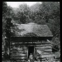 Image of Woman in front of cabin - Edward and Josephine Kemp Lantern Slide Collection