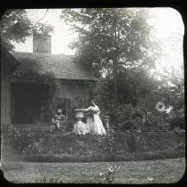 Image of Unidentified family in garden - Edward and Josephine Kemp Lantern Slide Collection