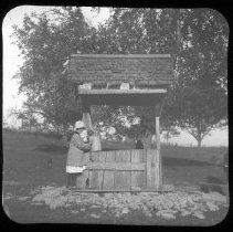Image of Young girl at well - Edward and Josephine Kemp Lantern Slide Collection