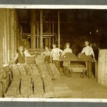 Image of Workers stand with stacks of tobacco twists - Ryan-Hampton Tobacco Company Photograph Collection