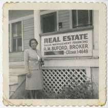 Image of Woman standing in front of real estate sign                                                                                                                                                                                                                    - Singleton Family Photograph Collection