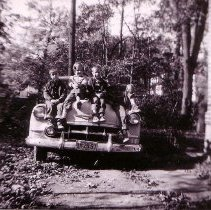 Image of 2009.128.20 - Mallett children [?], sitting on hood of a '53 Chevy