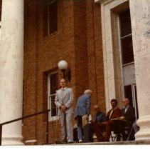 Image of Print, Photographic - Color photo of Administration bldg with man on steps speaking into a microphone.